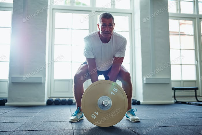Mature man in sportswear lifting weights alone in a gym