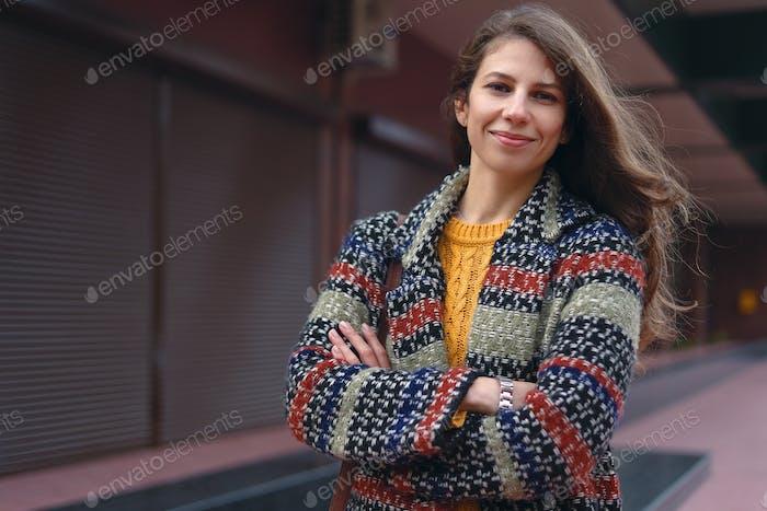 Junge Frau mit verschränkten Armen posiert auf städtischem Hintergrund