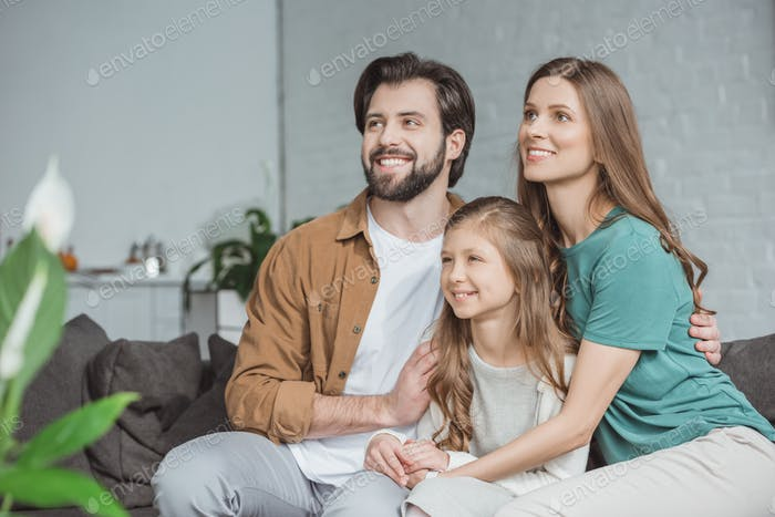 happy parents and daughter looking away at home