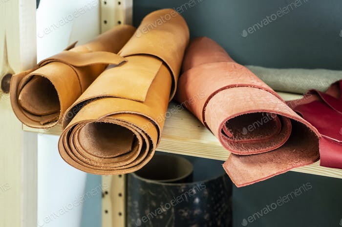 Many rolls leather on shelf in leather workshop.