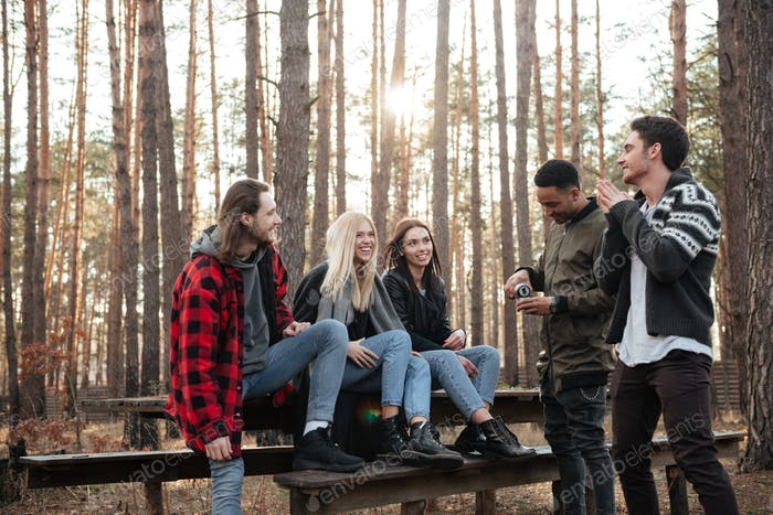 Lächelnde Gruppe von Freunden sitzen im Freien im Wald.