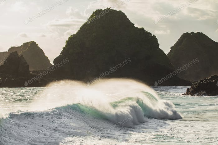 Huge crashing waves in sunset light with mountain view on horizon