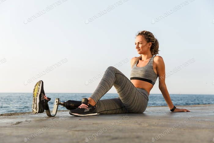 Amazing disabled sports woman sitting on the beach