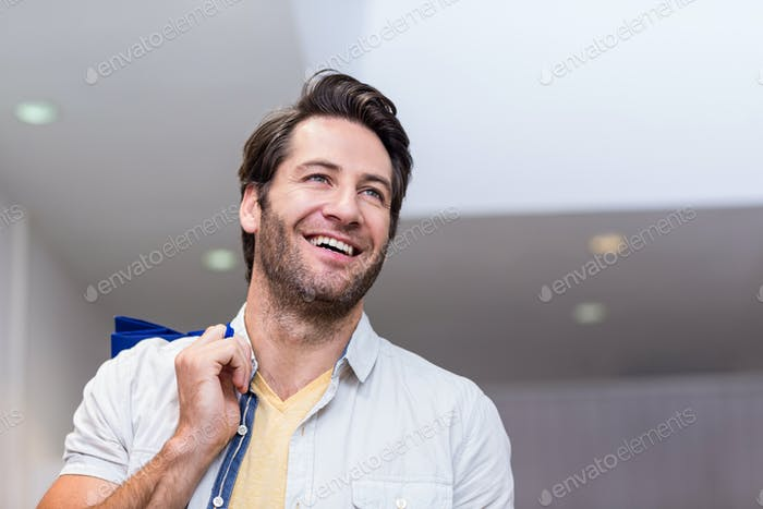 Smiling man with shopping bags in clothing store