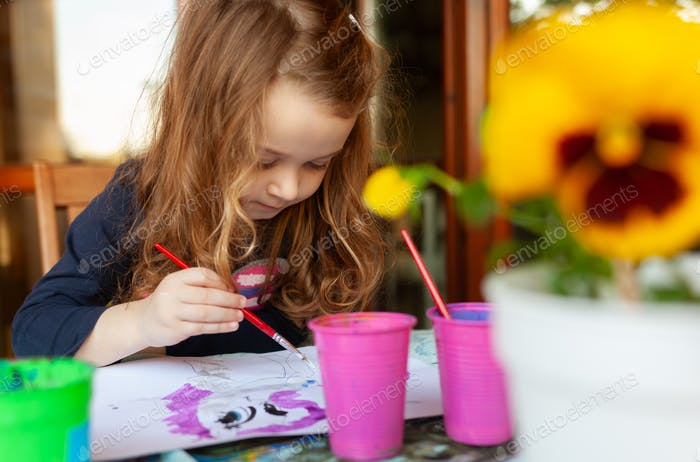Three year old girl paints with watercolors on the terrace.