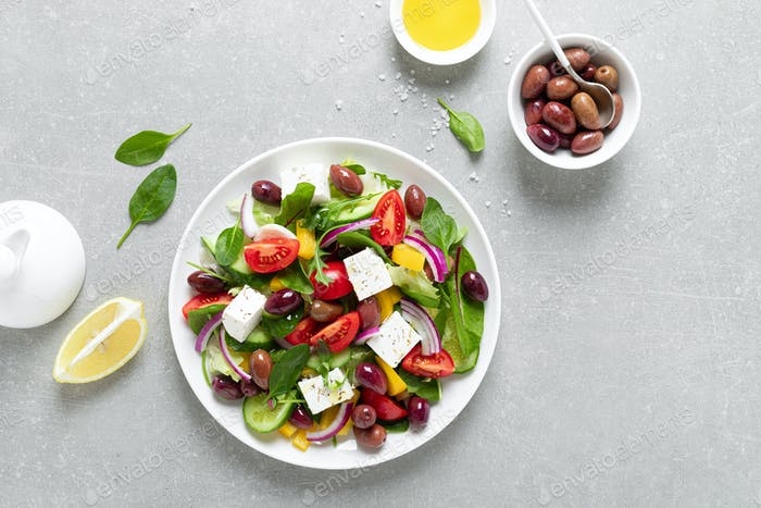 Greek salad with greens, olives and feta chesse on a white plate, top view