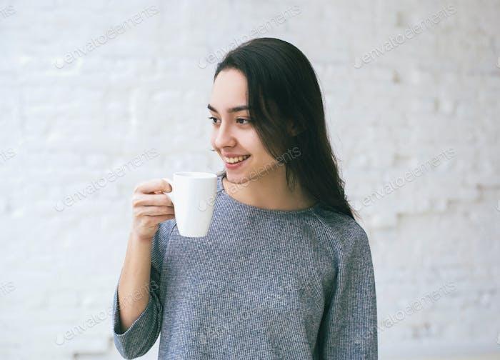 Junge schöne Mädchen Frau Porträt über Ziegelmauer mit Tasse