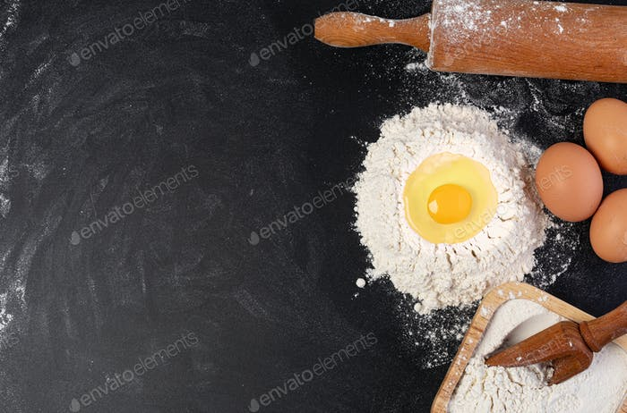 Rolling pin and white flour on a dark background
