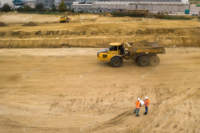 Top view of two road construction workers in orange vests and protective helmets