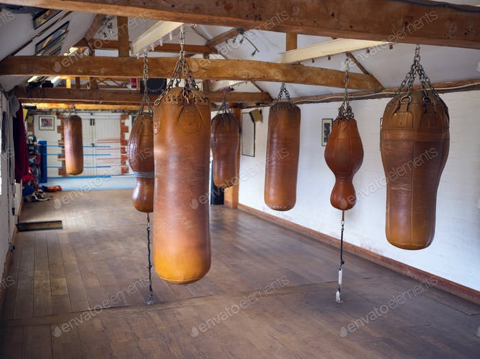 Empty Boxing Training Gym With Old Fashioned Leather Punch Bags