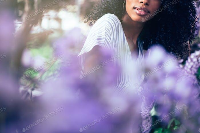 Junge schwarze Frau sitzt umgeben von Blumen