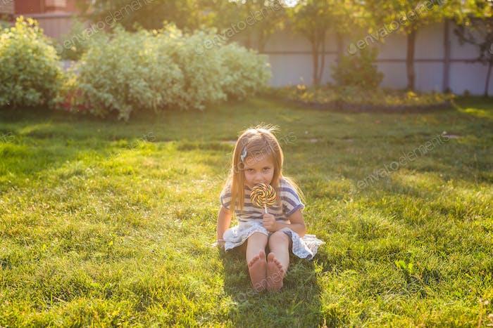 niedliches kleines Mädchen essen einen Lutscher auf dem Gras im Sommer.