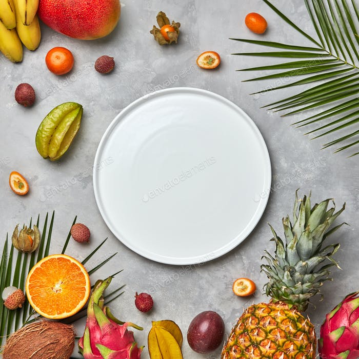 Palm leaves, empty white plate and a set of different tropical fruits mango, passion fruit,banana