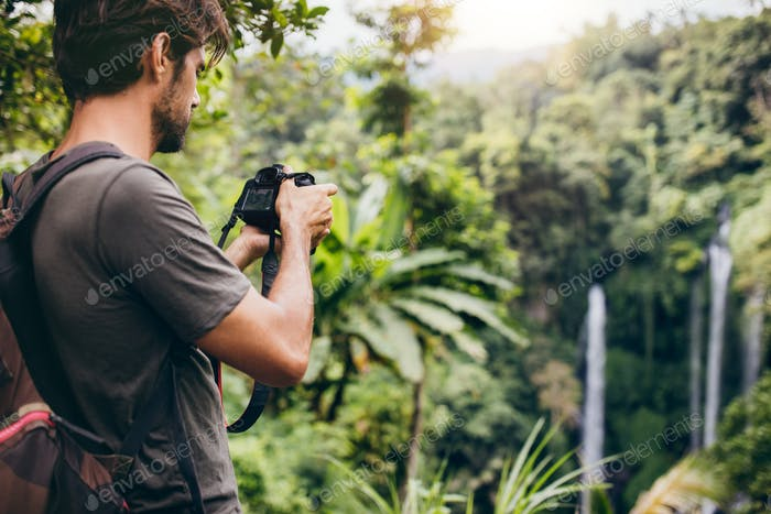 Man with backpack taking a photo of waterfall