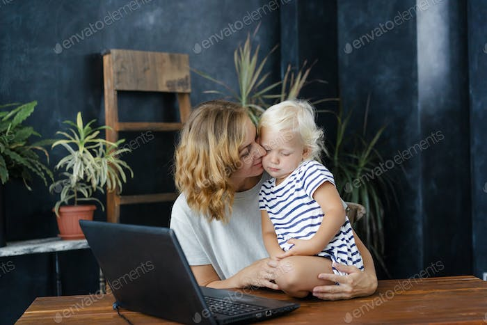 Mom lovingly hugs her daughter in the home office.