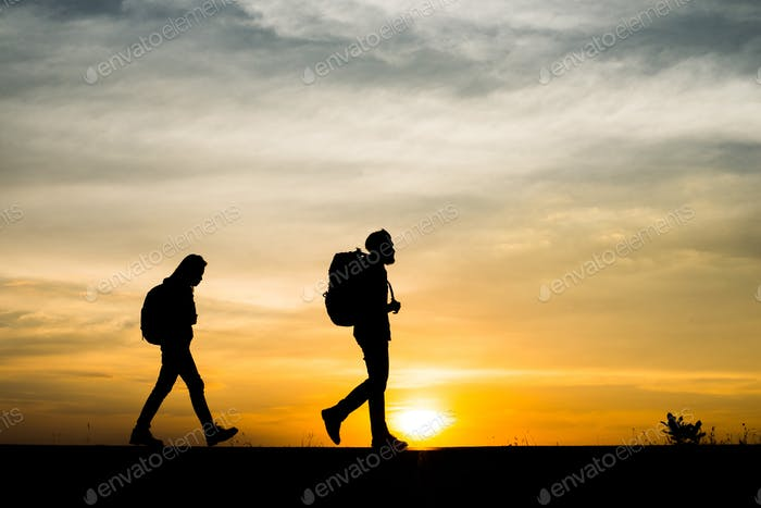 Silhouettes of two hikers with backpacks enjoying sunset. Travel concept.