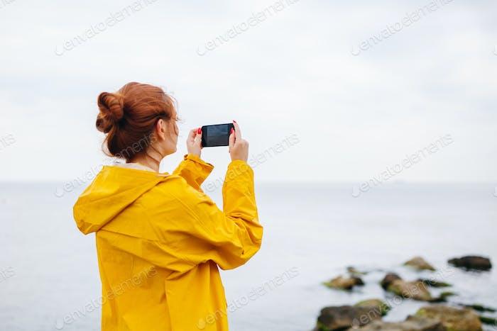 Girl taking photo of ocean