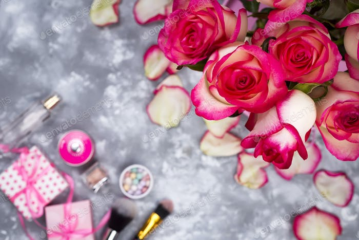 Frame of beautiful roses with cosmetics on gray concrete