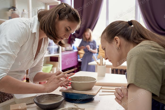 Workshop about training in pottery, one female teaches another