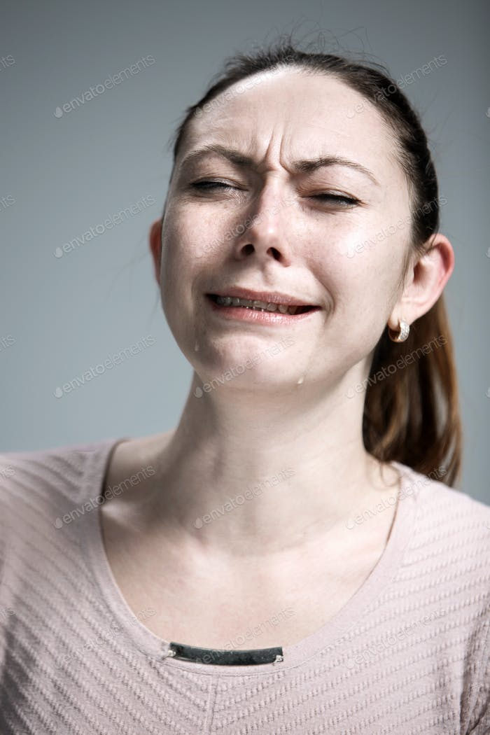 The crying woman with tears on face closeup