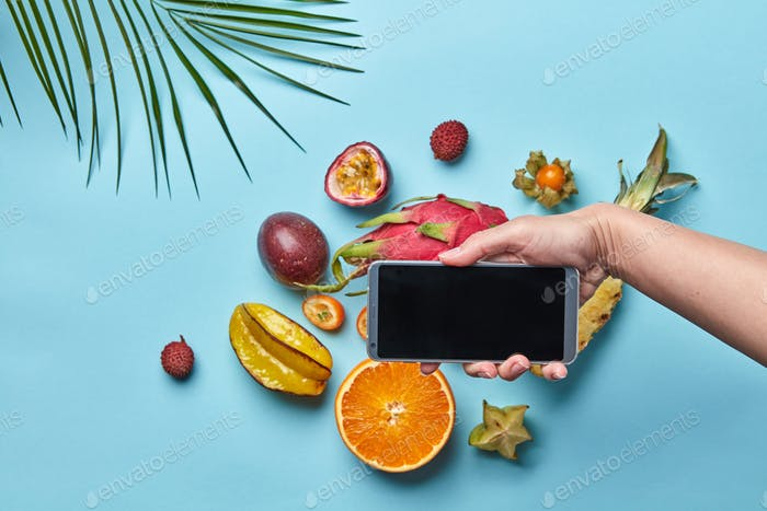 Set of different tropical fruits and palm leaf on a blue phonet with space for text. Woman's