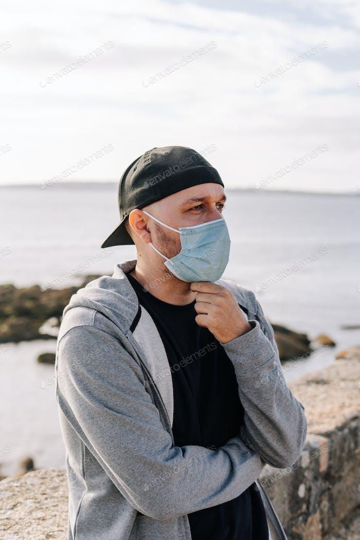 Tourist mit einer chirurgischen Maske in der Nähe des Ozeans