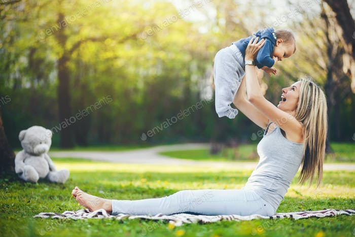 Delighted mother with her son outdoors in a park