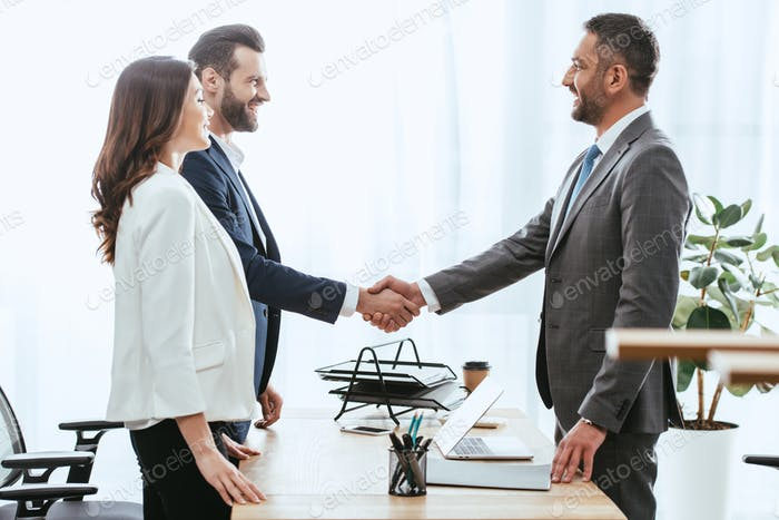 handsome advisor in suit shaking hands with investors at workplace