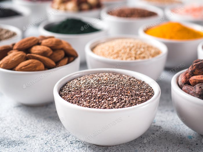 Chia seeds in small white bowl and other superfoods