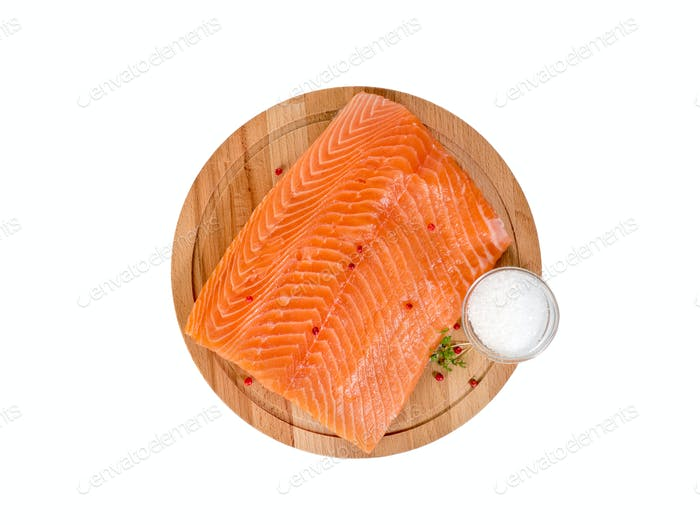 Fresh salmon fillet on wooden cutting board on white background, top view