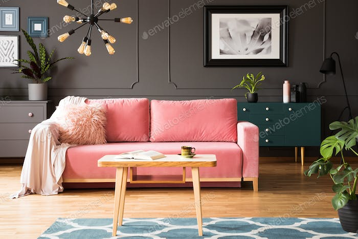 Poster on grey wall in living room interior with pink couch and