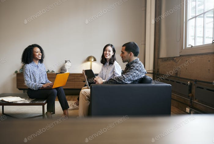 Smiling work colleagues using laptops at a casual meeting