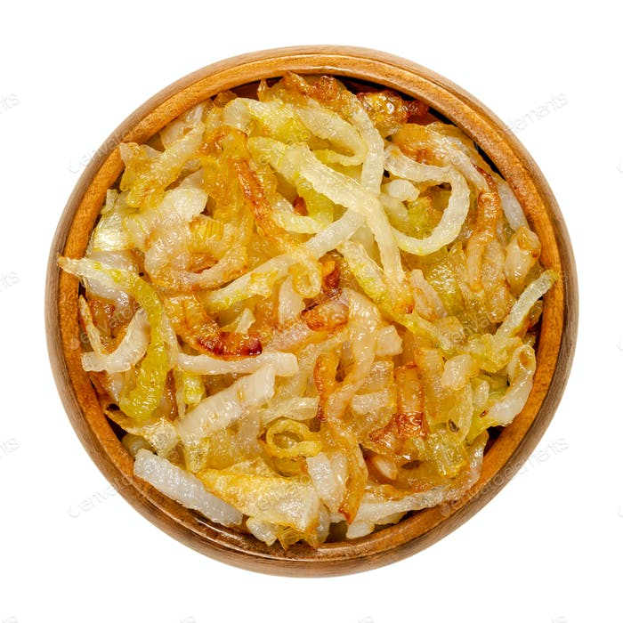 Onions, golden brown roasted, in a wooden bowl