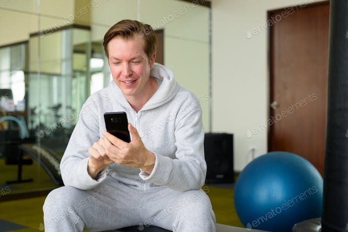 Happy young handsome man with hoodie using phone and sitting at the gym