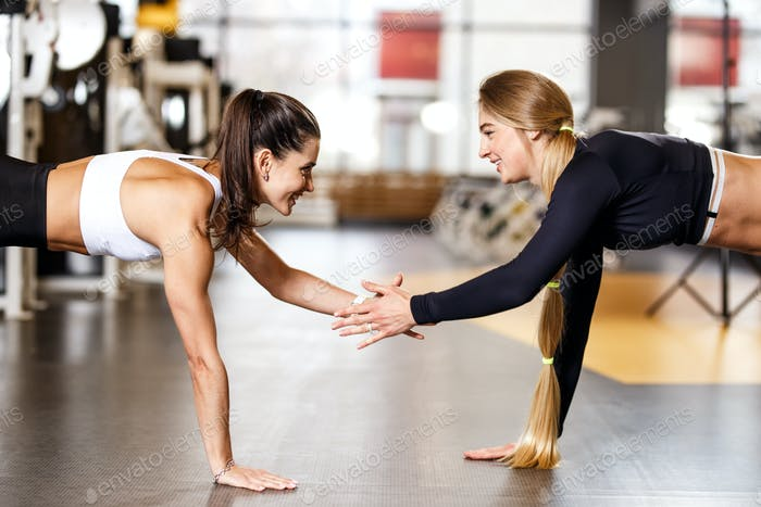 Two young athletic girls dressed in sportswear are doing plank and holding hand in hand in the