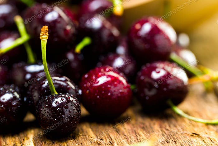 Berries of a sweet cherry in a wooden plate on a background of boards