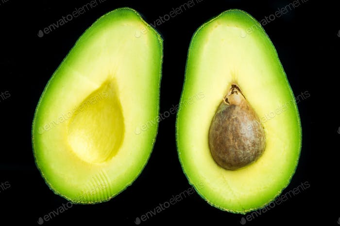 Avocado halves on dark background,flat lay
