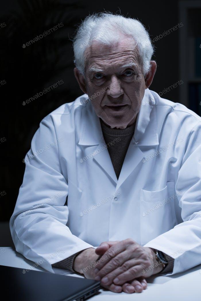 Elder man in medical apron
