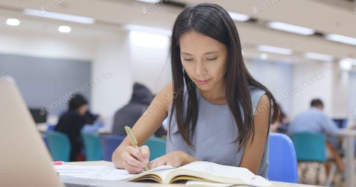 Frau schreiben auf Notiz in der Universitätsbibliothek