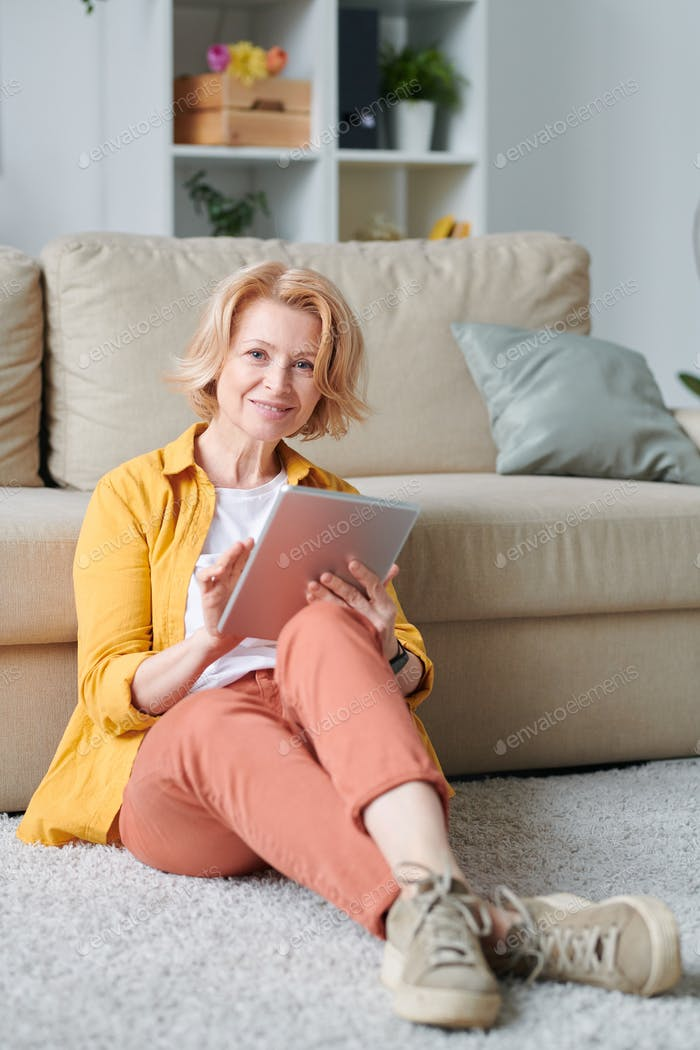 Blond mature female in casualwear sitting on the floor by couch and using tablet