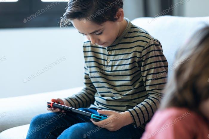 Kleiner Junge spielt Video spiele, während er zu Hause auf dem Sofa sitzt.