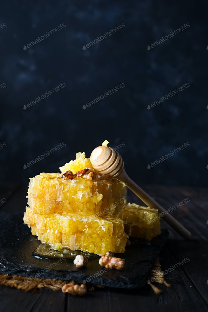 Honeycomb with honey dipper and nuts over dark background with copy space