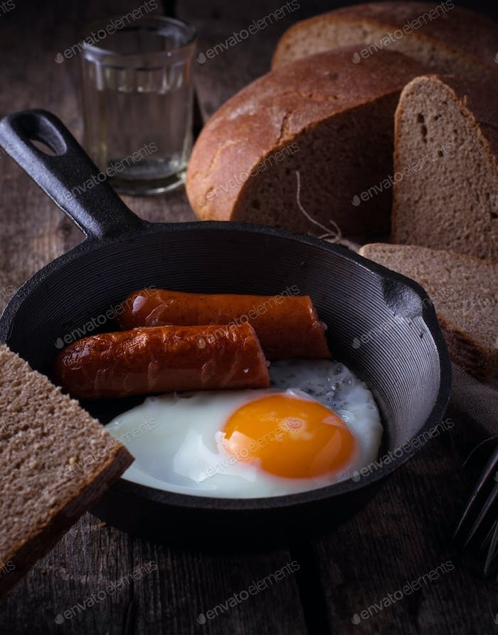 Fried eggs with sausages in a pan