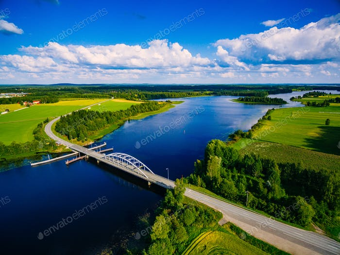 Aerial view on bridge over blue lake in rural Finland countryside with green and yellow fields