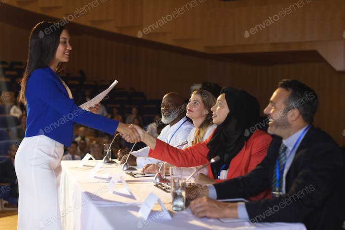 Business woman shaking hand to the business colleague in the auditorium