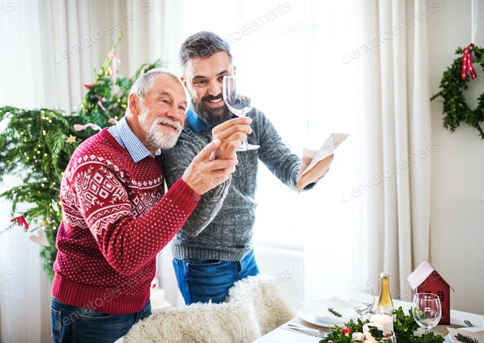 A senior father and adult son setting a table for dinner at Christmas time.