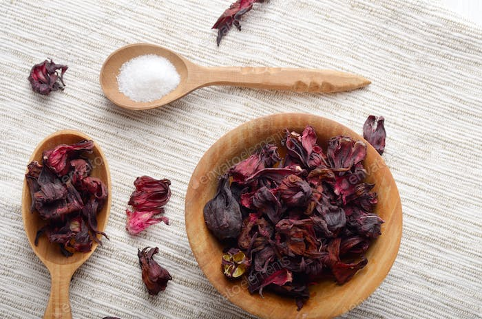 Top view at wooden bowl and spoon of dry hibiscus petals on line