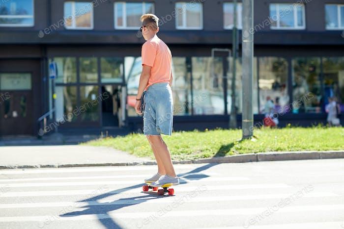 teenage boy on skateboard crossing city crosswalk