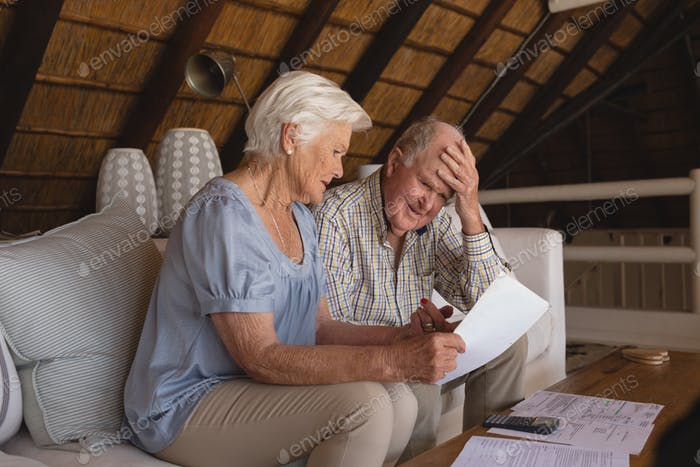 Side view of worried senior couple discussing over medical bills in living room at home