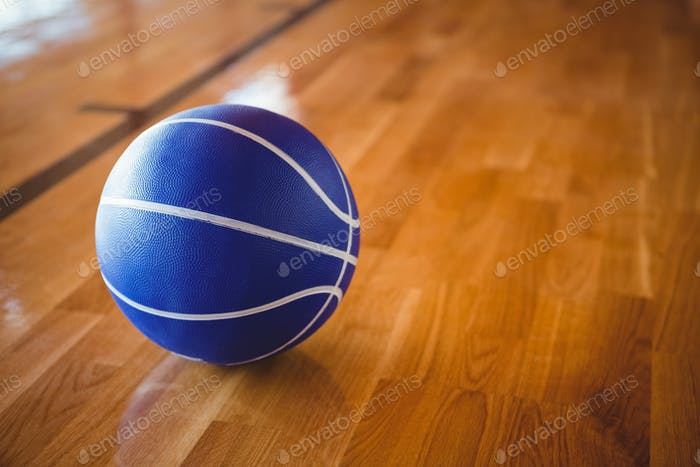 Close up of blue basketball on hardwood floor